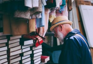 A man going through books and clothes.