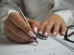 A woman writing down moving tips.