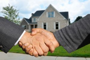 Two man shaking hands in front of the house