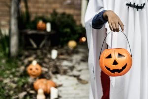 girl carrying a Halloween pumpkin