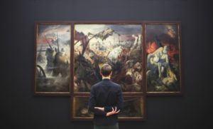 man standing in front of a painting