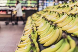 A stand of bananas in a supermarket.