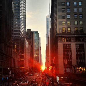 A view of a street in Manhattan during sunset.