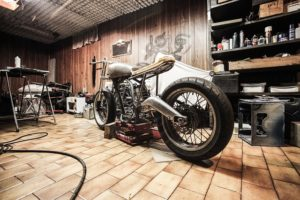 A garage with a motorbike.