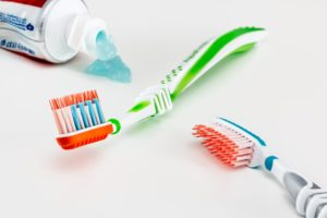Two toothbrushes and a paste.