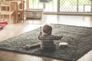 Child playing on a carpet in the living room - safe and sound with some baby proofing assistance.