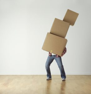 A man carrying three cardboard boxes. Something you can find in a packing guide for an easy move is getting all the needed supplies.