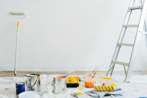 Paints, ladder and containers laid out for painting the wall. Painting the walls is a good way to add value to your home.