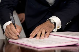 Man in a suit signing a contract. Here are some things you should check before you sign a moving contract.