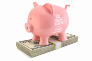Piggy bank on a stack of dollars. Here are some ways to reduce moving costs.