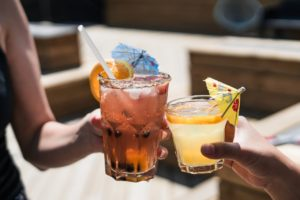 two persons holding cocktails