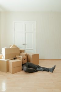 man sitting in moving boxes
