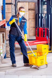 a girl in a uniform cleaning the warehouse with a mop and bucket