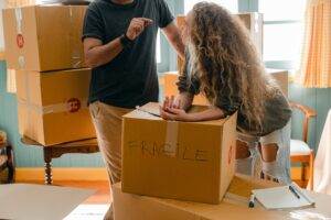 Woman and man near different boxes for moving