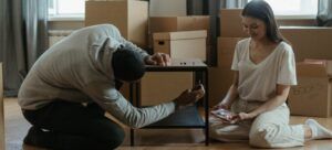 A couple disassembling furniture