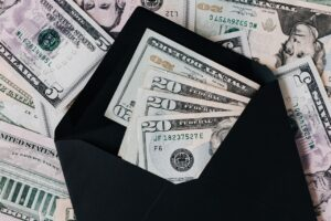 Black envelope with dollar bills inside and outside it
