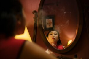 A woman looking herself in the mirror
