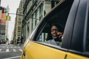 A man talking on the phone inside a cab