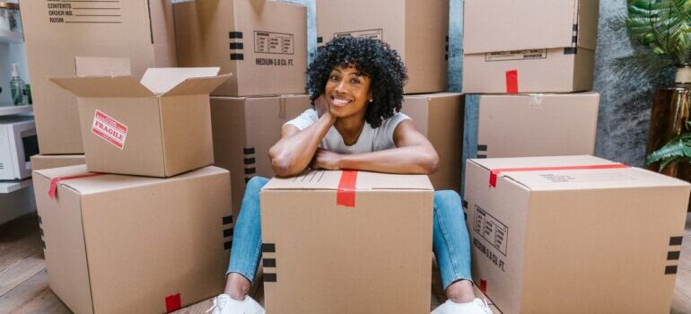 woman sitting in front of a pile of boxes