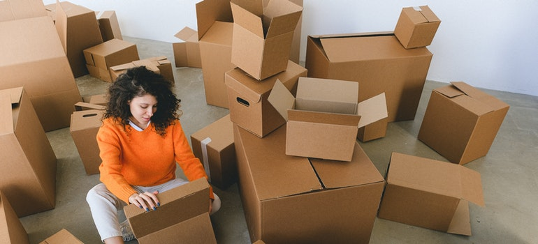 a woman sitting among moving boxes