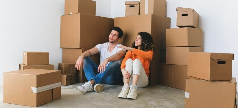 couple sitting in front of moving boxes