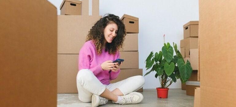 woman waiting for Upper East Side movers to finish unloading moving boxes