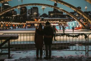 Two people looking at people ice skating